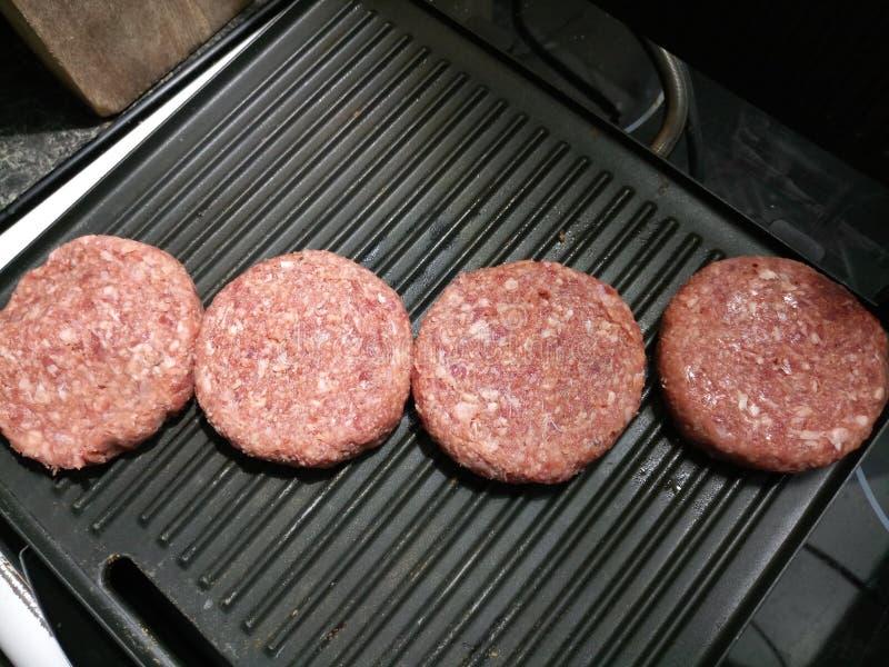 Hamburgers roses crus de boeuf sur le gril photographie stock