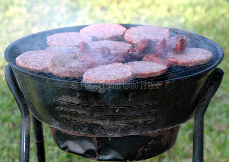 Hamburgers, sausages grilling. Hamburgers, sausages grilling on a barbecue royalty free stock images