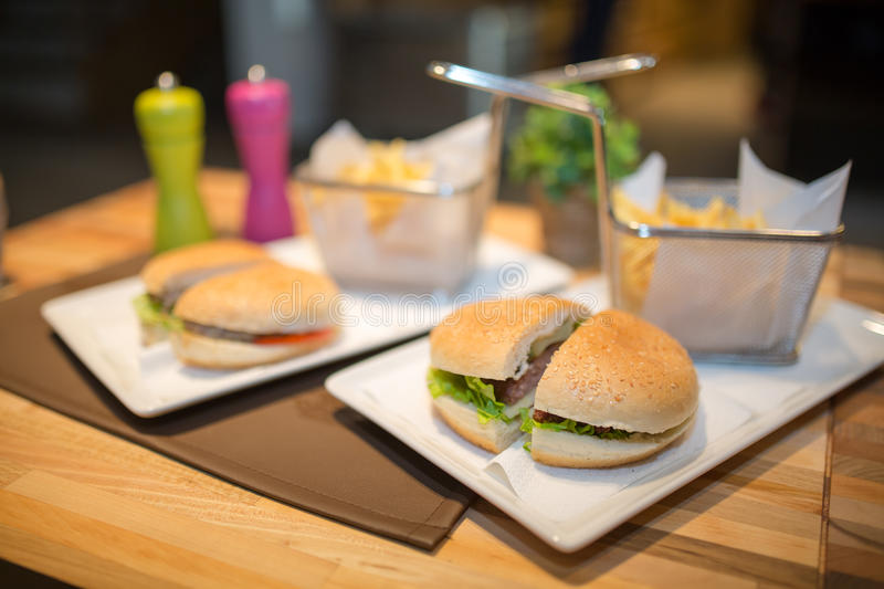 Hamburgers served with fries.Colorful.Hamburger with beef meet, vegetables, ketchup and chips on plate.Unhealthy,fatty food royalty free stock photography