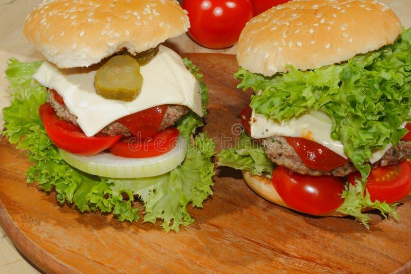 Hamburgers, snel voedsel, hamburger, hamburgerlapje vlees, sla, tomaat, stock afbeelding