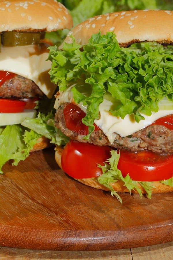 Hamburgers, snel voedsel, hamburger, hamburgerlapje vlees, sla, tomaat, royalty-vrije stock afbeeldingen
