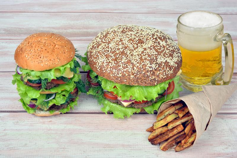 Hamburgers with a glass of beer and french fries stock image