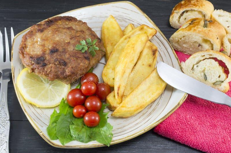 Hamburgersteak mit Kartoffeln, Kirschtomaten und olivgrünem Brot O lizenzfreies stockfoto