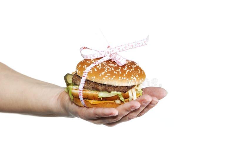 Hamburgeru cheeseburger w rękach z miarą taśmy odizolowywającej na białym tle Zdrowy ciężar straty diety pojęcie obraz royalty free