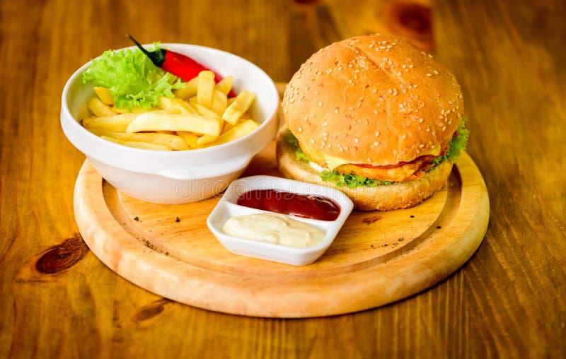 Hamburgeru menu Wysoka kalorii przekąska Hamburgeru i francuza dłoniaki i pomidorowy kumberland na drewnianej desce Fasta food po zdjęcie royalty free