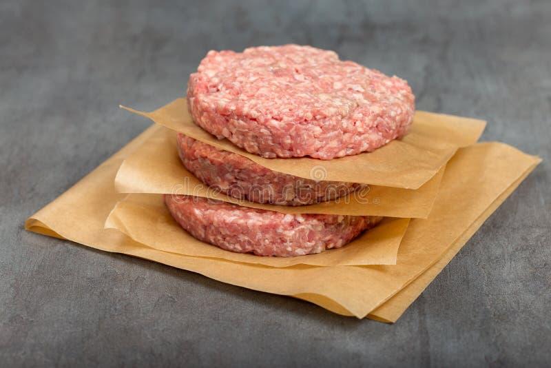 Hamburgeru mięso na popielatym tła zakończeniu up fotografia royalty free