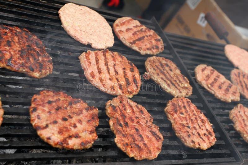 Hamburgeru opieczenie na ogieniu Domowej roboty hamburgery Grillów klopsiki Robić hamburgerom Plenerowi na grillu Grilla grilla p fotografia stock