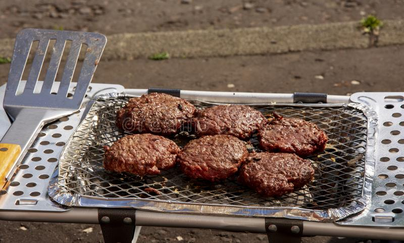 Hamburgery gotuje na przenośnego urządzenia BBQ obraz stock