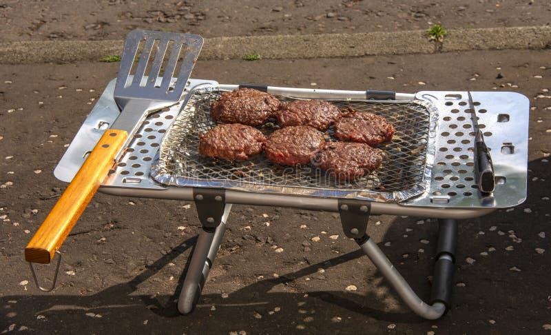 Hamburgery gotuje na przenośnego urządzenia BBQ obrazy stock