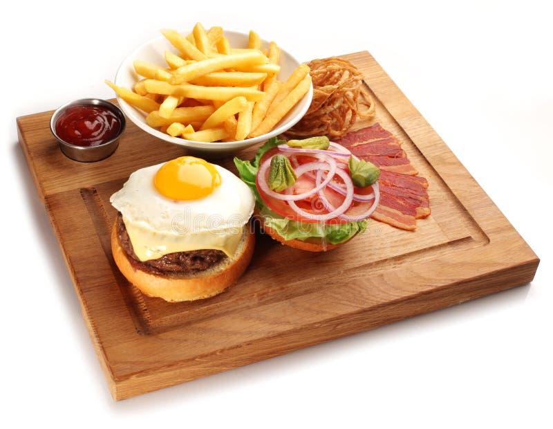 Hamburgery i francuz smażą na drewnianej tacy obrazy royalty free