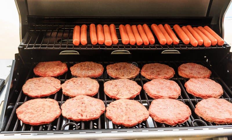 Hamburgery i hot dog na grillu zdjęcia royalty free