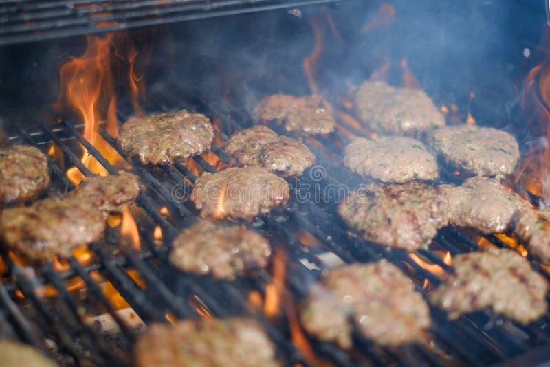 Hamburgery na grillu, płomienny grilla grill z hamburgerami zdjęcia stock