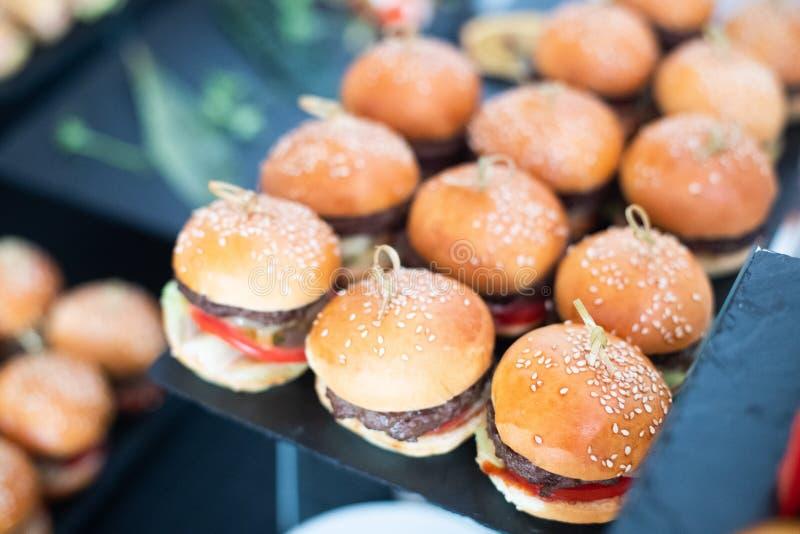 Hamburgery na stole Mali hamburgery na tacy szef kuchni poj?cia karmowa ?wie?a kuchni oleju oliwka nad dolewania restauraci sa?at fotografia stock