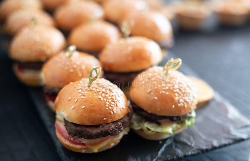 Hamburgery na stole Mali hamburgery na tacy szef kuchni poj?cia karmowa ?wie?a kuchni oleju oliwka nad dolewania restauraci sa?at zdjęcia stock