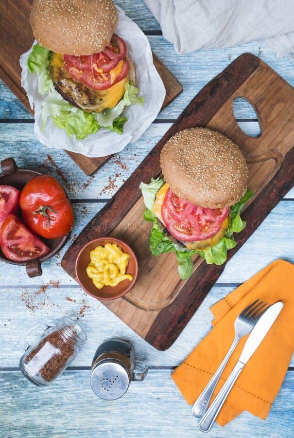 Hamburgery na stole, musztardzie i pomidorze, zdjęcie stock
