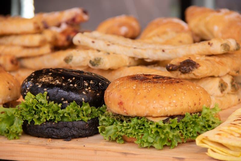 Hamburgery z mąką, mięsnymi cutlets i zieleniami białą i czarną, żadny uliczni karmowi festiwale obrazy royalty free