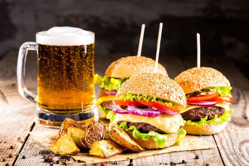 Hamburgery z wołowiną, smażący szkło zimny piwo i grule i fotografia stock