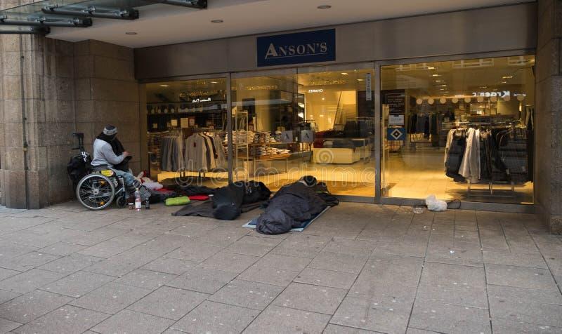 hamburgo O os sem-abrigo dorme cedo na manhã na rua ao lado das lojas caras em vagabundos de um sono imagem de stock royalty free