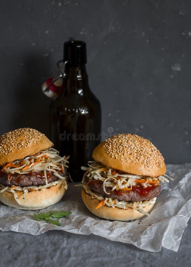 Hamburguer asiático com ketchup do hoisin e pimentão Mayo e cerveja em um fundo cinzento Estilo asiático foto de stock