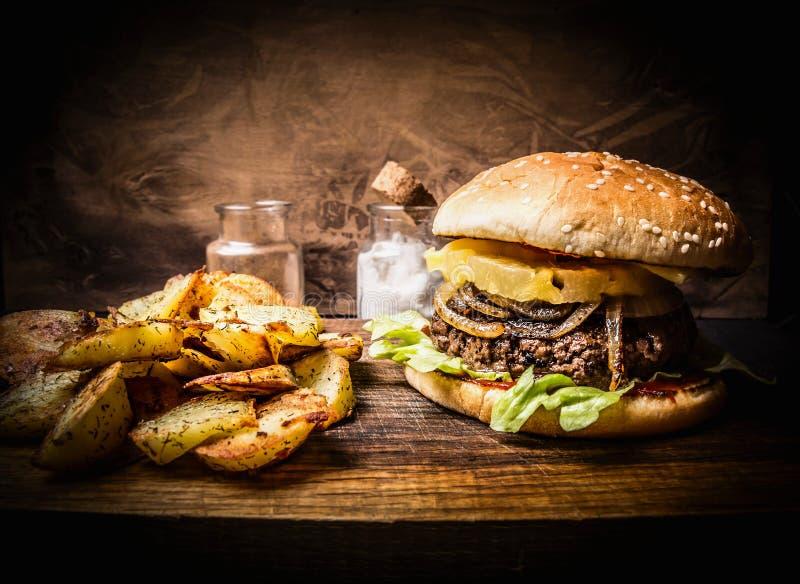 Hamburguer caseiro delicioso com carne, cebolas, alface e abacaxi, cunhas da batata no fim rústico de madeira da placa de corte a fotos de stock