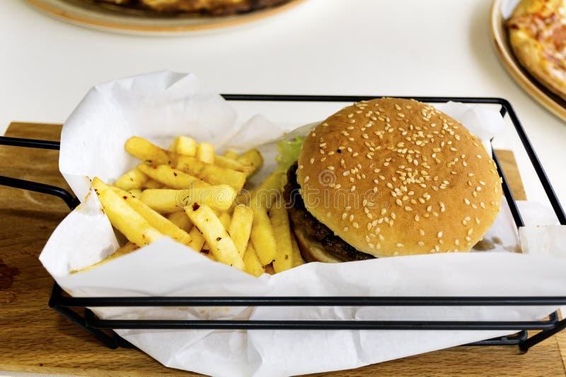 Hamburguer com batatas fritas em um restaurante - comida lixo fotos de stock royalty free