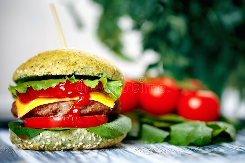 Hamburguer com bolo verde e os legumes frescos imagem de stock