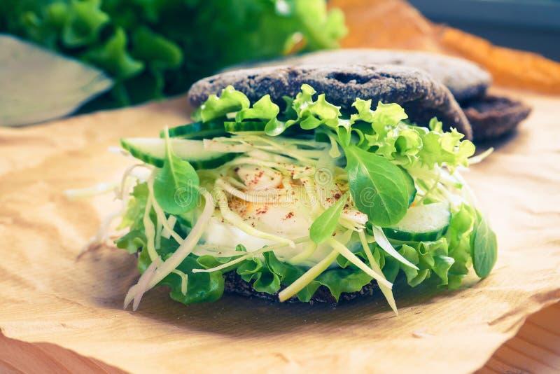 Hamburguer com pão dos vegetais, do ovo cozido e de centeio Conceito do alimento saudável comer ou de vegetariano foto de stock
