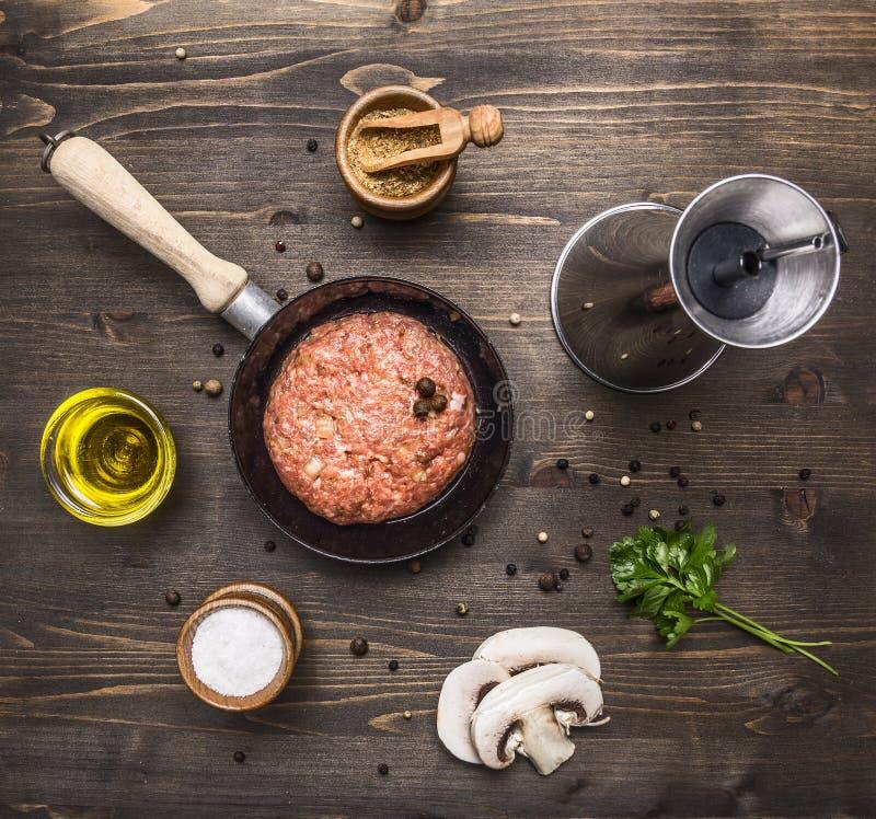 Hamburguer cru para uma frigideira pequena, tempero da costoleta, manteiga, cogumelos, fim rústico de madeira da opinião superior fotografia de stock