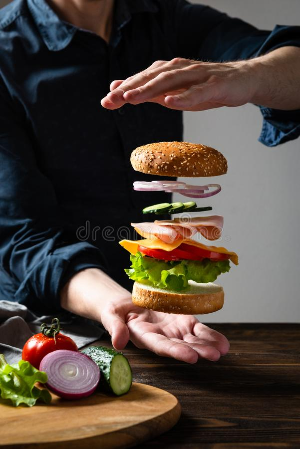 Hamburguer da levita??o entre as m?os em um fundo escuro Ingredientes de voo hamburguer ou cheeseburger acima da placa Espa?o par fotos de stock royalty free