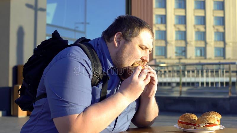 Hamburguer de mastigação masculino excesso de peso, almoço insalubre do escritório, problemas da digestão imagens de stock