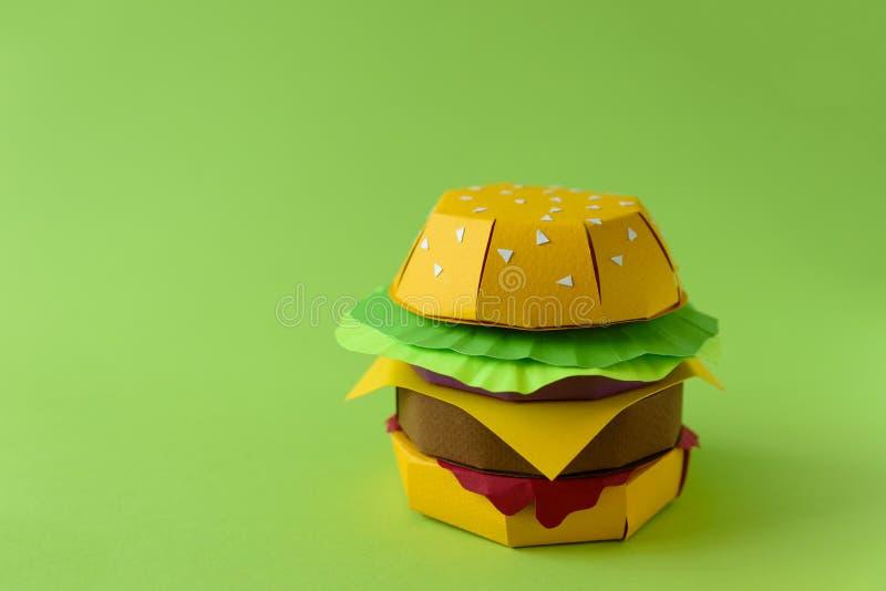 Hamburguer de papel com carne, queijo, alface e cebolas em um fundo verde Copie o espaço Conceito criativo ou da arte do alimento foto de stock