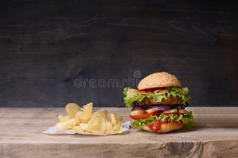 Hamburguer delicioso com as microplaquetas da carne, do tomate, do queijo, da alface e de batata no contador de madeira Copie o e fotografia de stock