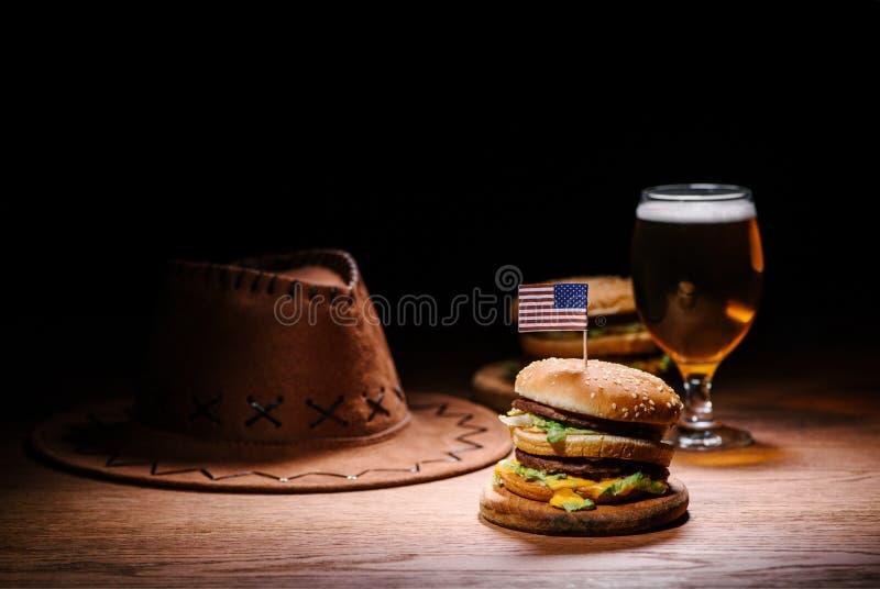 hamburguer delicioso na tabela de madeira com vaqueiro americano fotografia de stock royalty free