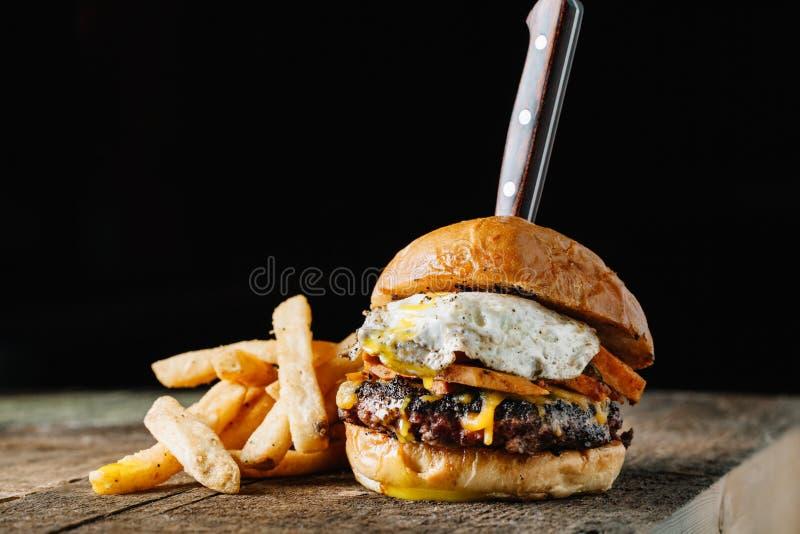 Hamburguer do café da manhã com um ovo frito na superfície rústica escura, horizo foto de stock royalty free