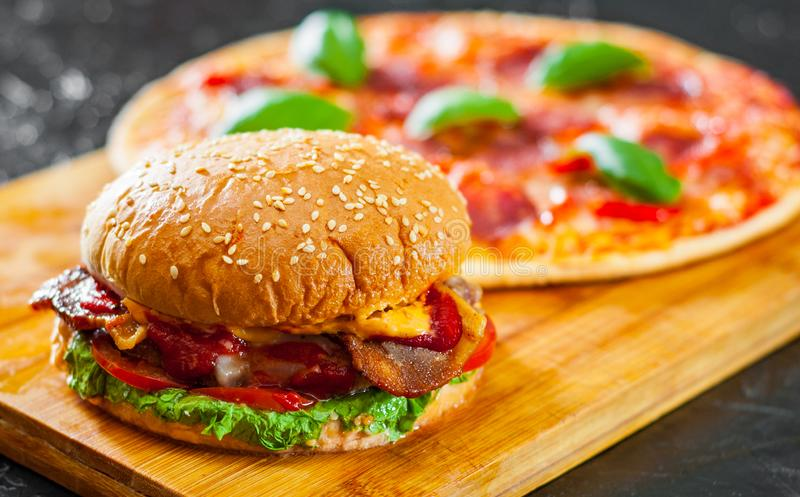 Hamburguer do queijo do bacon com a cebola e a pizza do tomate do rissol de carne com mozzarella, presunto, tomates, salame, pime fotografia de stock royalty free