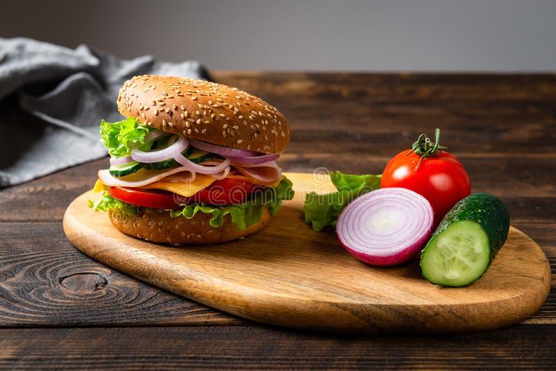 Hamburguer do sanduíche com presunto, queijo e vegetais em uma placa de madeira com ingredientes Copie o espaço foto de stock royalty free