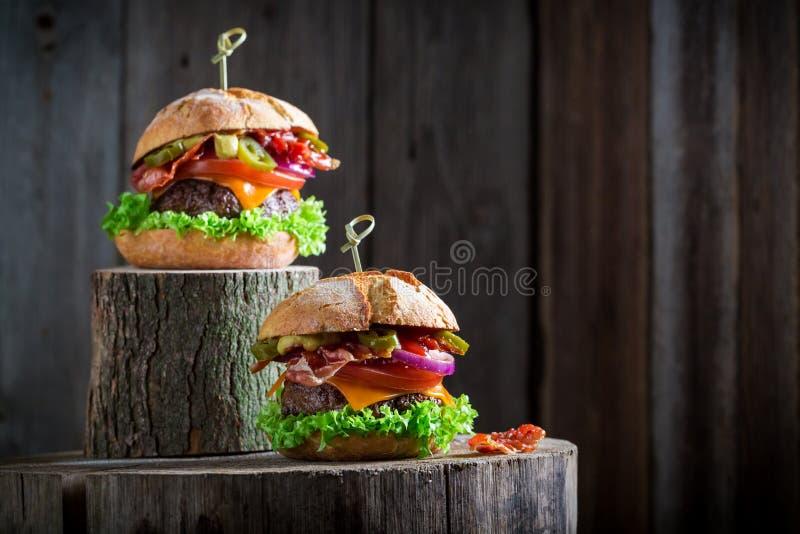 Hamburguer dois com cebola, tomate e alface, microplaquetas e bacon imagem de stock