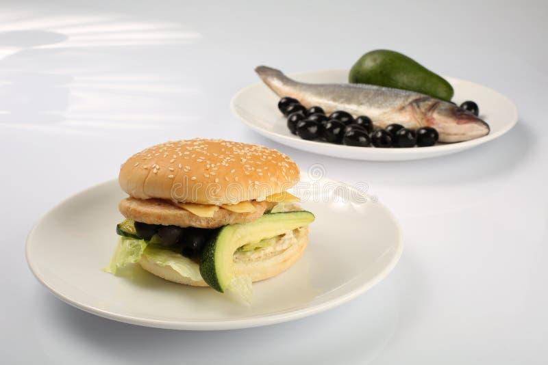 Hamburguer dos peixes com abacate e azeitonas, fatias de queijo, temperadas com molho e salada verde para um menu do restaurante imagem de stock royalty free