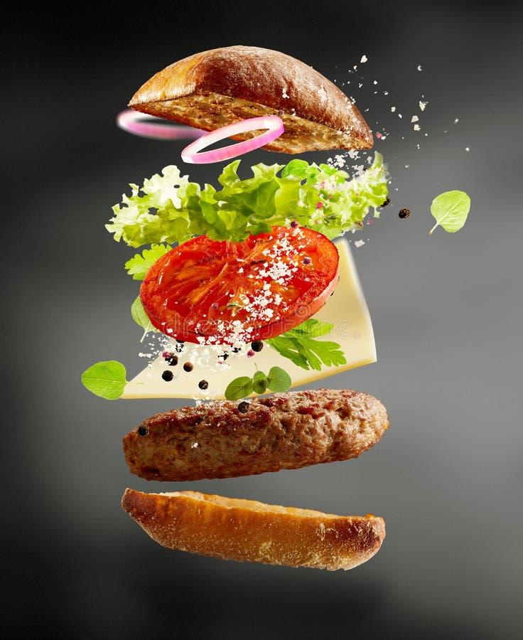 Hamburguer grelhado da carne com ingredientes de flutuação foto de stock
