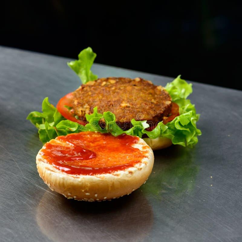 Hamburguer morno do falafel com alface, tomate, a cebola vermelha e o tzatziki fotografia de stock royalty free