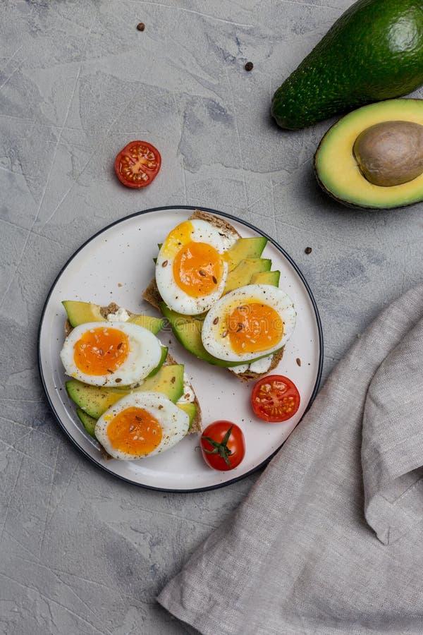 Hamburguer no pão da grão com ovo cozido e abacate na placa no fundo cinzento imagem de stock royalty free
