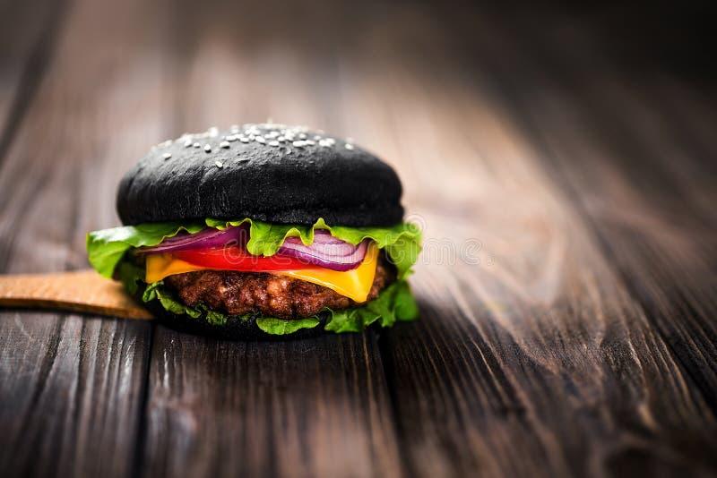 Hamburguer preto caseiro com queijo Cheeseburger com o bolo preto no fundo de madeira escuro fotografia de stock royalty free