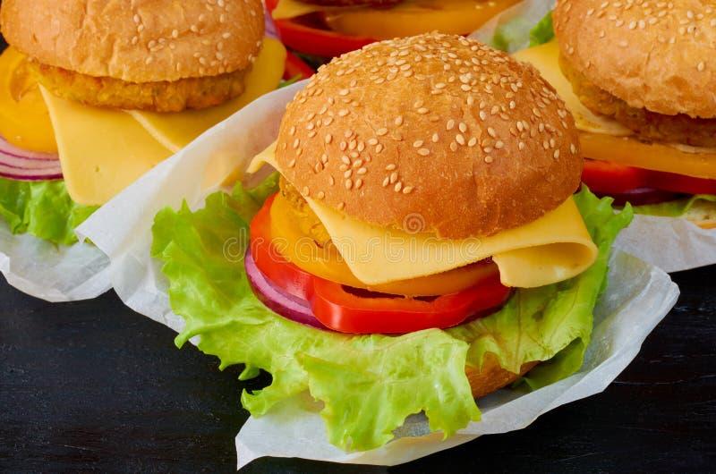 Hamburguer quente do vegetariano com falafel, salada, queijo e tomates no fundo preto Fast food americano tradicional imagens de stock royalty free