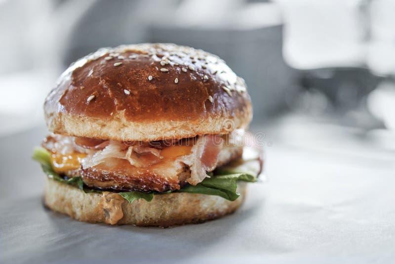 Hamburguer suculento do bacon em um fundo borrado cinzento fotografia de stock royalty free