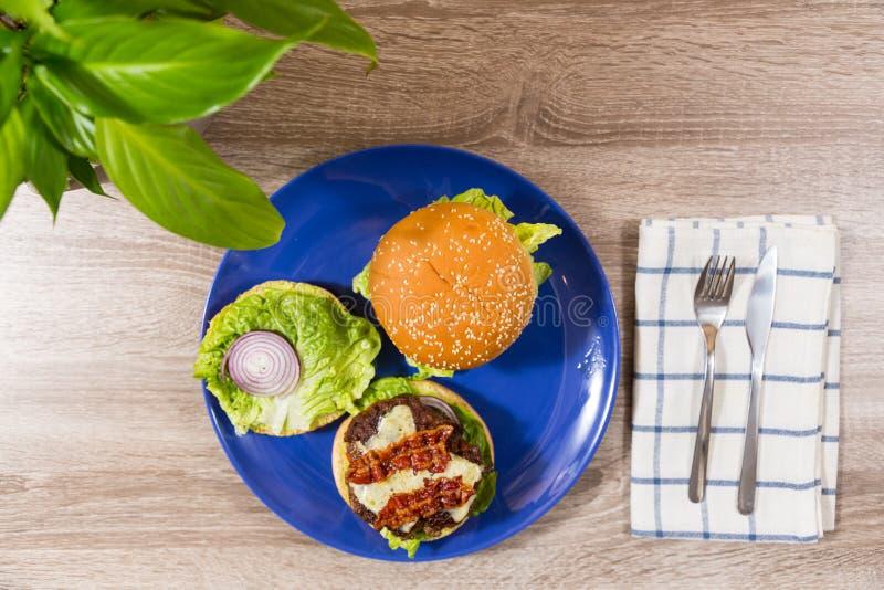 Hamburgueres da vista superior dois com queijo do bacon da cebola vermelha da alface no sesa imagem de stock