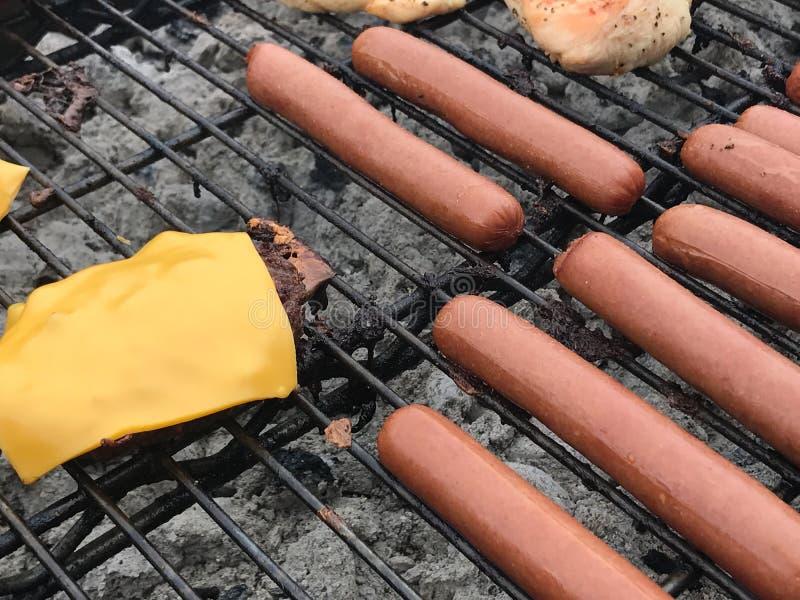 Hamburgueres e Hotdogs em uma grade imagem de stock royalty free