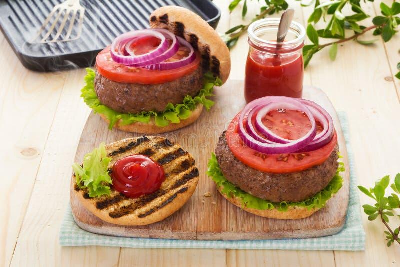 Hamburgueres grelhados com tomates imagens de stock