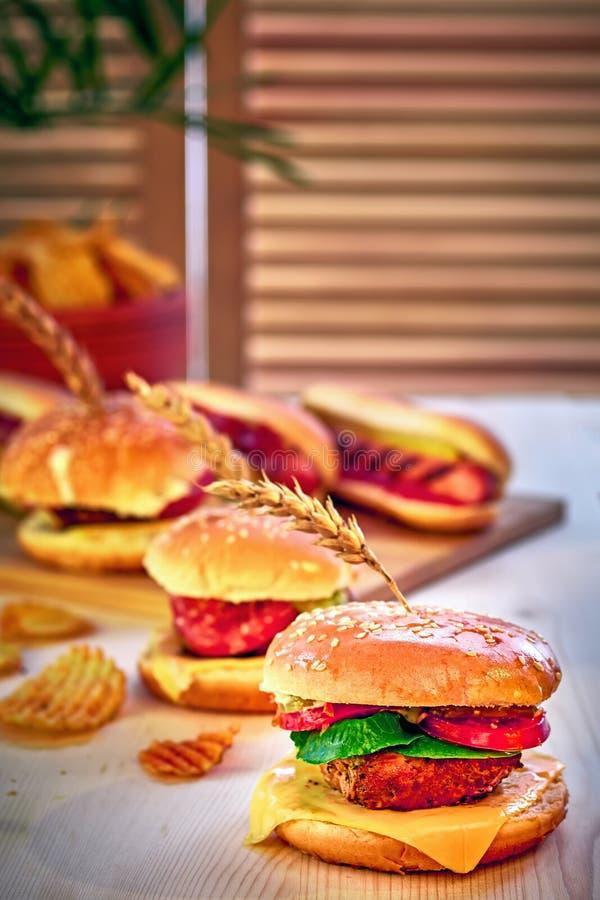 Hamburgueres grelhados saborosos da carne com alface, tomate, queijo e maionese na tabela de madeira rústica A casa fez gamburger fotografia de stock