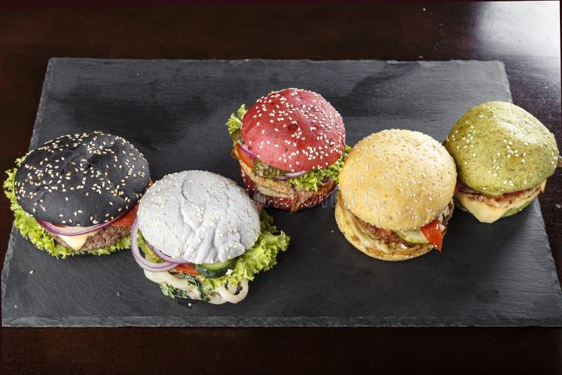 hamburgueres Multi-coloridos na tabela imagem de stock