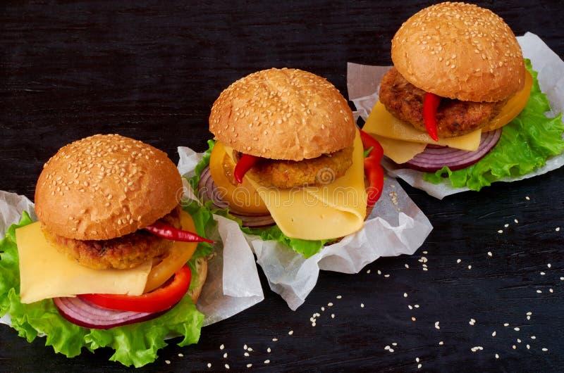 Hamburgueres saborosos com falafel, salada, anéis de cebola, queijo, tomates e sésamo no fundo preto Fast food americano clássico fotos de stock
